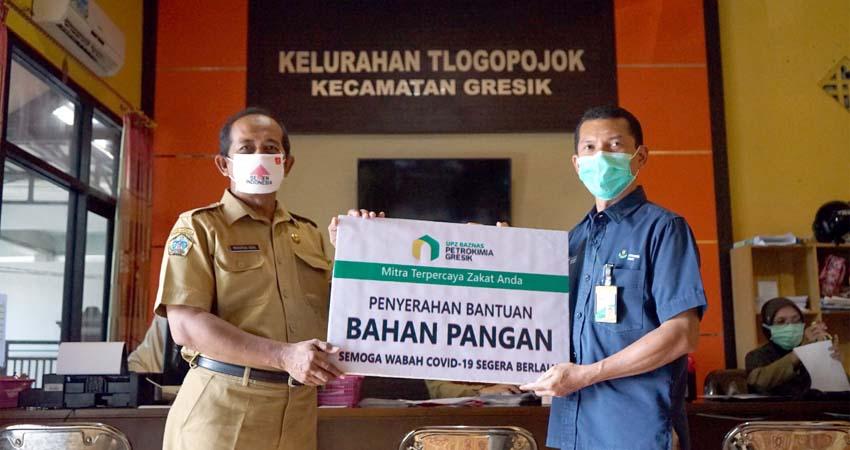 Penyerahan bantuan secara simbolis oleh Ketua UPZ Baznas Petrokimia Gresik (kanan) kepada Lurah Tlogopojok (kiri)